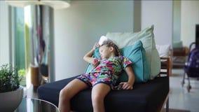 Het meisje ligt op de leunstoel dichtbij het panoramische venster en is bored, langzame motie stock videobeelden
