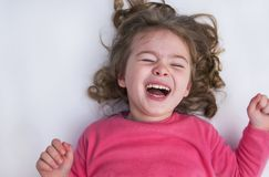 Het meisje ligt op de witte vloer en de glimlach stock fotografie