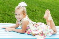 Het meisje ligt op een blauwe bank en glimlacht Stock Foto's