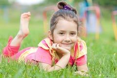 Het meisje ligt op een gras stock afbeeldingen