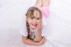 Het meisje ligt op een vloer en glimlacht Royalty-vrije Stock Foto