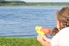 Het meisje ligt op het gras in de straat en schiet een pistoolwater, close-up, achtermening royalty-vrije stock fotografie