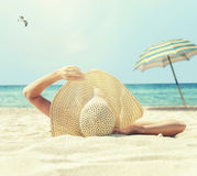 Het meisje ligt op het witte zand op het strand Stock Foto's