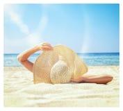 Het meisje ligt op het witte zand op het strand Stock Fotografie