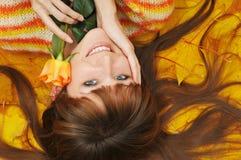 Het meisje ligt op hoop van gele bladeren stock foto