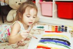 Het meisje ligt op slaapkamervloer en verfbeeld stock afbeeldingen