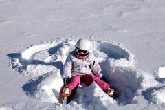 Het meisje ligt op sneeuw. De engel van de sneeuw Royalty-vrije Stock Foto