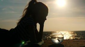 Het meisje ligt op het strand en bekijkt zijn favoriete vissen in aquarium stock footage