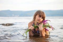 Het meisje ligt op het strand met een boeket van kleur Mooie mening, de zomerdag stock afbeeldingen