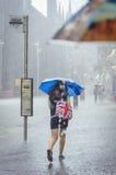 Het meisje loopt bij de zomerregen in de stad royalty-vrije stock foto's