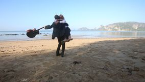 Het meisje loopt gebaarde gitarist op strand de achterstand in hij haar en draaien rond neemt stock footage