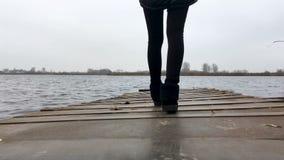 Het meisje loopt langs de pijler door het meer stock videobeelden