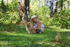 Het meisje loopt met haar geliefde hond in het hout in een zonnige de zomerdag Meisje die in hoed haar Spitz koesteren royalty-vrije stock fotografie