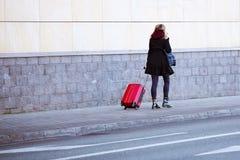 Het meisje loopt op de stoep met een rode reiszak op wielen Bagage jonge toerist in een moderne modieuze koffer De reiziger is bi royalty-vrije stock foto