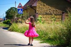 Het meisje loopt op de weg in het dorp Stock Afbeeldingen
