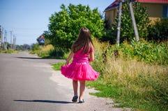 Het meisje loopt op de weg in het dorp Stock Foto's
