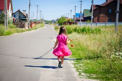 Het meisje loopt op de weg in het dorp Stock Foto