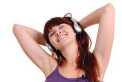 Het meisje luistert aan muziek Stock Foto