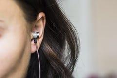 Het meisje luistert aan muziek in hoofdtelefoons Oorclose-up royalty-vrije stock fotografie
