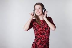 Het meisje luistert aan muziek met hoofdtelefoons en het dansen stock foto's