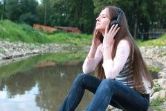 Het meisje luistert muziek in hoofdtelefoon openlucht Stock Fotografie