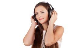 Het meisje luistert muziek in hoofdtelefoons Royalty-vrije Stock Afbeeldingen