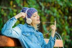 Het meisje luistert muziek in park Melodiegeluid en mp3 Het concept van de muziekventilator De hoofdtelefoons moeten modern gadge stock afbeeldingen