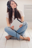 Het meisje luistert muziekzitting op de vloer in de Studio Terwijl cro Stock Foto