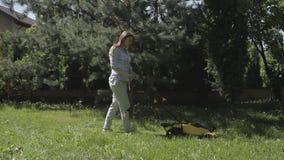 Het meisje maait een ongelijk gazon met gele blootvoetse grasmaaier stock video