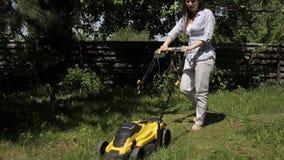 Het meisje maait een ongelijk gazon met gele blootvoetse grasmaaier stock videobeelden