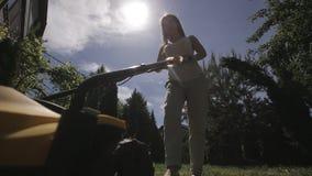 Het meisje maait een ongelijk gazon met gele blootvoetse grasmaaier stock footage