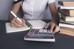 Het meisje maakt berekeningen stock foto