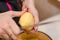 Het meisje maakt de aardappels schoon Thuis het koken Natuurlijke producten Het koken van een schotel van aardappels royalty-vrije stock foto's