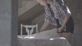 Het meisje maakt de nietmachine zachte stoffering op de zetel voor de stoel vast stock videobeelden