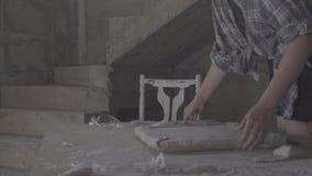 Het meisje maakt de nietmachine zachte stoffering op de zetel voor de stoel vast stock footage