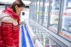 Het meisje maakt een aankoop bij kruidenierswinkelhypermarket royalty-vrije stock afbeeldingen