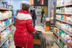 Het meisje maakt een aankoop bij kruidenierswinkelhypermarket royalty-vrije stock fotografie