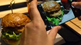 Het meisje maakt een foto van hamburger en tomatesap op een smartphone in koffie dichte omhooggaand stock videobeelden
