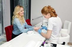 Het meisje maakt een manicure stock afbeelding