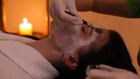 Het meisje maakt een masker voor gezicht in de schoonheidssalon stock video