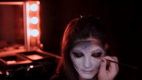 Het meisje maakt een samenstelling in de stijl van een heks Halloween stock footage