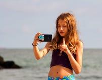 Het meisje maakt een selfie op het overzeese strand Stock Fotografie