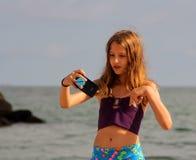 Het meisje maakt een selfie op het overzeese strand Royalty-vrije Stock Foto