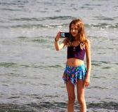 Het meisje maakt een selfie op het overzeese strand Royalty-vrije Stock Afbeeldingen