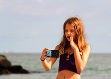 Het meisje maakt een selfie op het overzeese strand Stock Foto