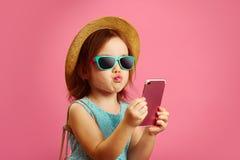 Het meisje maakt een selfieportret op telefoon, trekt haar lippen aan de camera, draagt een binnen geklede strohoed en zonnebril, royalty-vrije stock foto's
