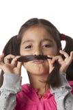 Het meisje maakt een snor van haar haar Stock Foto's