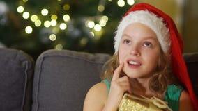 Het meisje maakt een wens voor Kerstmis Dicht portret van bruin-eyed meisje in santahoed met giftdoos in handen Kerstmis stock videobeelden