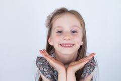 Het meisje maakt gezichten Grappige en gelukkige uitdrukkingen Het hebben van pret Kleuter in kleding op witte achtergrond stock fotografie