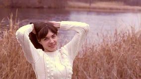 Het meisje maakt haar haar in sweater koud brunette recht stock footage